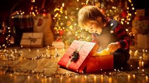 Kép egy karácsonyi ajándékát bontogató gyermekről.
